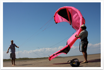 Kiteboarding instructor teaching student on the sand flats of south padre